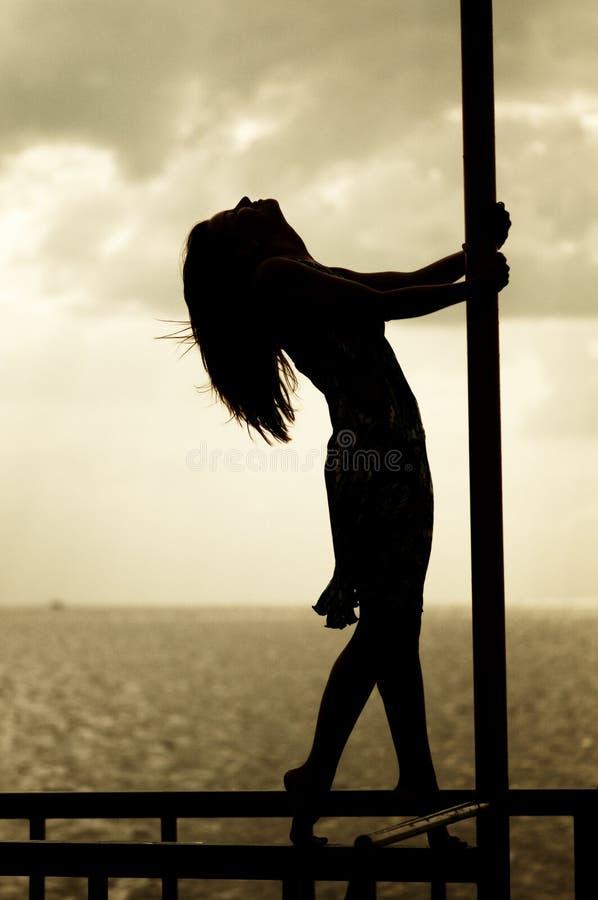 Photo de silhouette de fille au-dessus de mer de coucher du soleil image stock