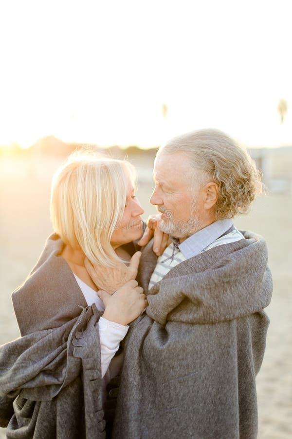 Photo de soleil du mari supérieur caucasien étreignant le plaid de port d'épouse sur la plage de sable photo stock