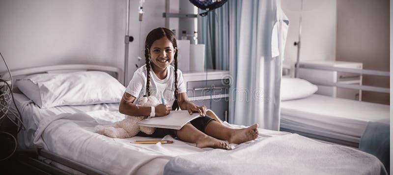 Photo de sourire de dessin de fille dans un livre images stock