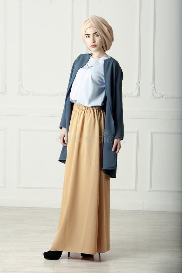 Photo de studio d'un type oriental de belle jeune femme intégral, sur un fond clair, habillé dans le style musulman image stock