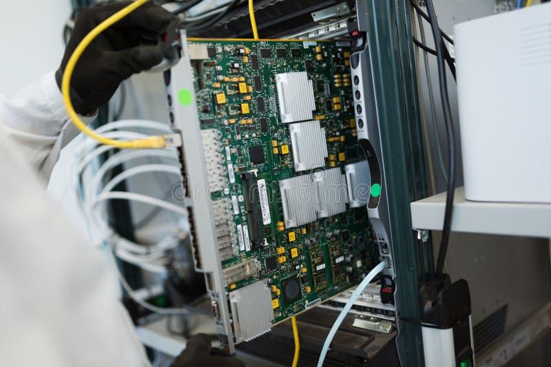 Photo de technicien réparant des cartes de mise en réseau de cmts image libre de droits