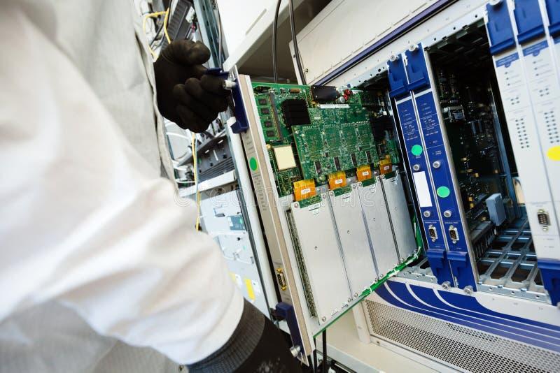 Photo de technicien réparant des cartes de mise en réseau de cmts photos libres de droits