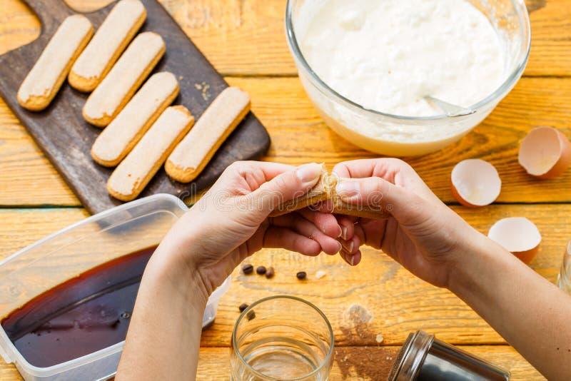Photo de tiramisu faisant cuire, mains humaines avec des biscuits de savoyardi images libres de droits