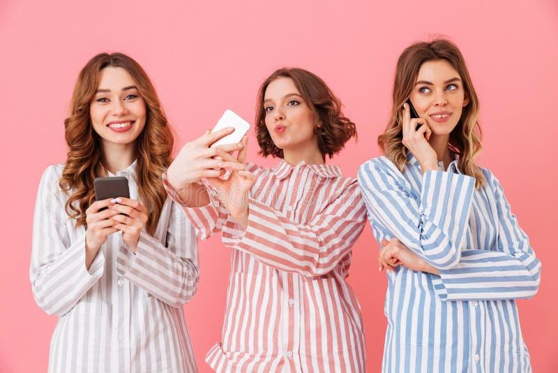 Photo de trois jeunes filles magnifiques 20s portant rayé coloré photos libres de droits