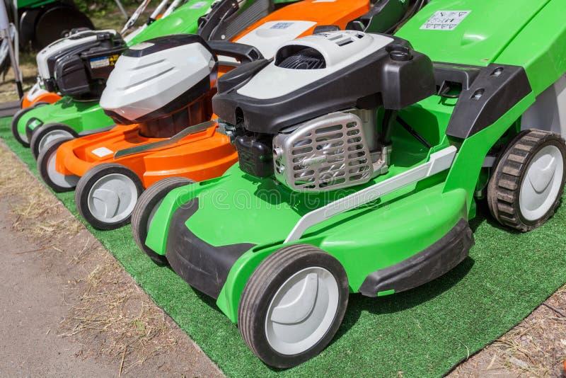 Photo de trois nouveau vert puissant et tondeuse à gazon orange d'essence photo libre de droits