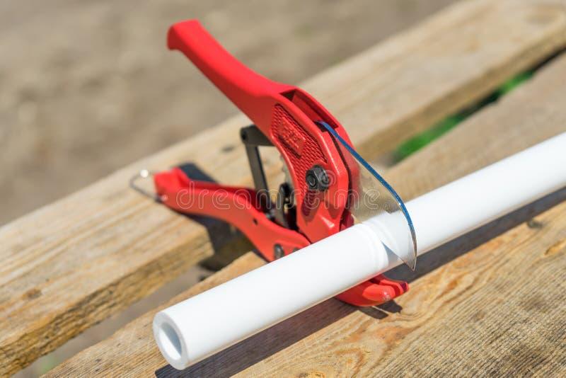 Photo de tuyau en plastique de coupe par des ciseaux rouges spéciaux photos stock