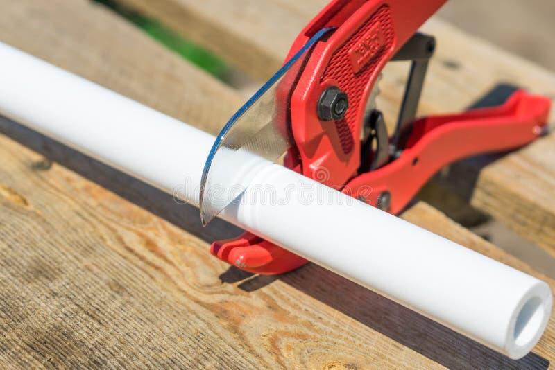 Photo de tuyau en plastique de coupe par des ciseaux rouges spéciaux photographie stock