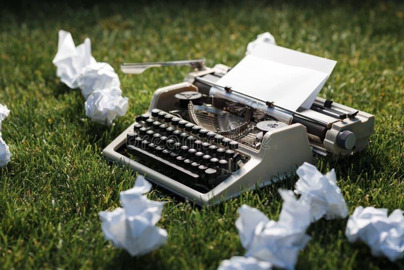 Photo de vieille machine à écrire sur une herbe verte avec une feuille de papier photo stock