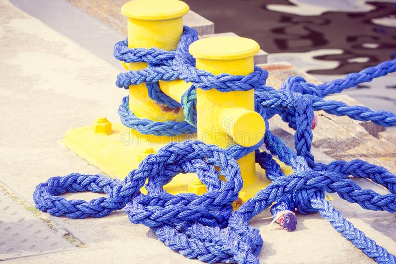 Photo de vintage, corde bleue et borne d'amarrage dans le port maritime, concept de plaisance photographie stock libre de droits