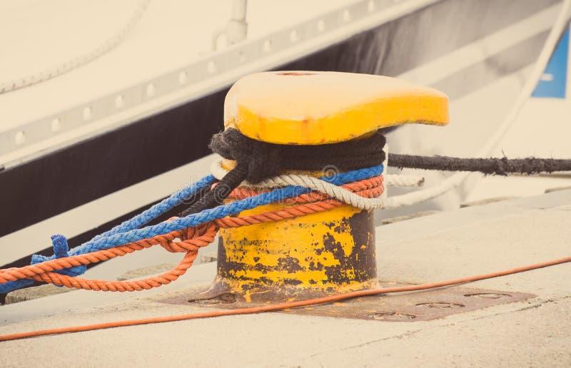 Photo de vintage, détail de la plaisance, corde colorée avec la vieille borne d'amarrage dans le port maritime photos libres de droits