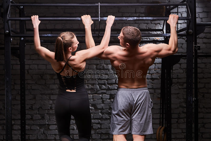 Photo de vue arrière de l'homme et de la femme musculaires faisant des exercices sur la barre horizontale contre le mur de brique photographie stock libre de droits