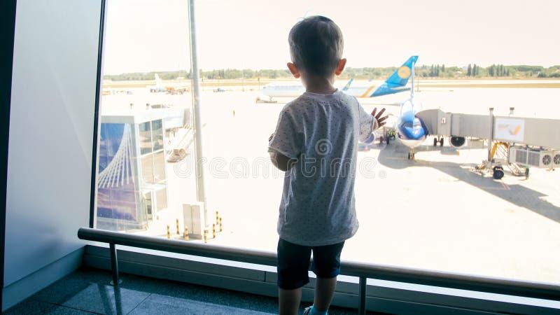 Photo de vue arrière de petit garçon regardant sur la piste l'aéroport par la grande fenêtre images libres de droits