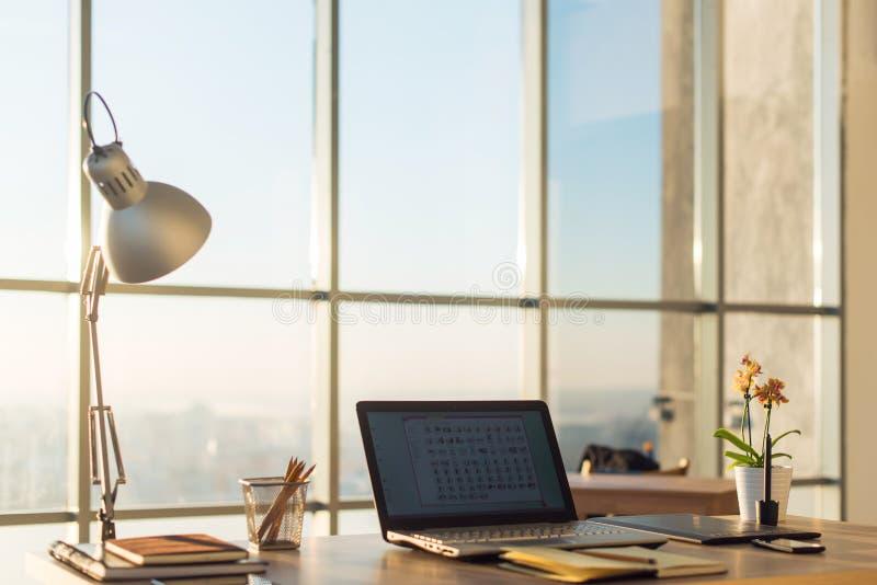 Photo de vue de côté de lieu de travail de studio avec le carnet vide, ordinateur portable Table de travail confortable de concep images libres de droits