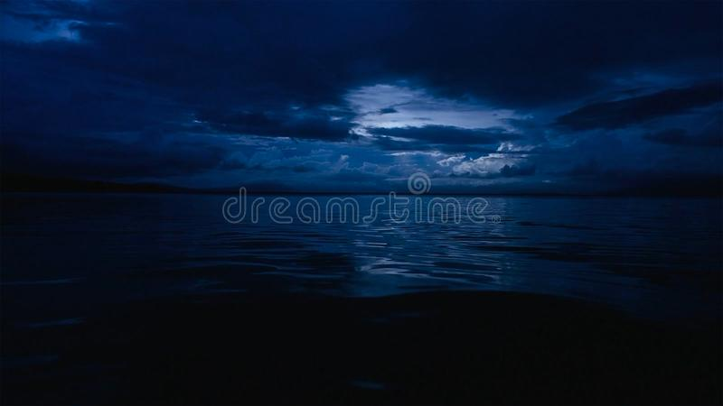 This photo of a deep blue moonlit ocean at night with calm waves stock images