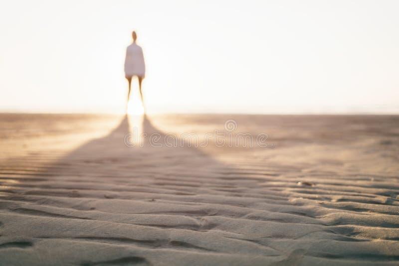 Photo Defocused de fille se tenant sur la plage photo stock