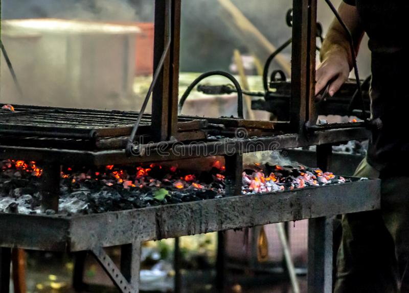 Photo depicting people making a grilled meat immersed in smoke. fire and coals.  stock photo