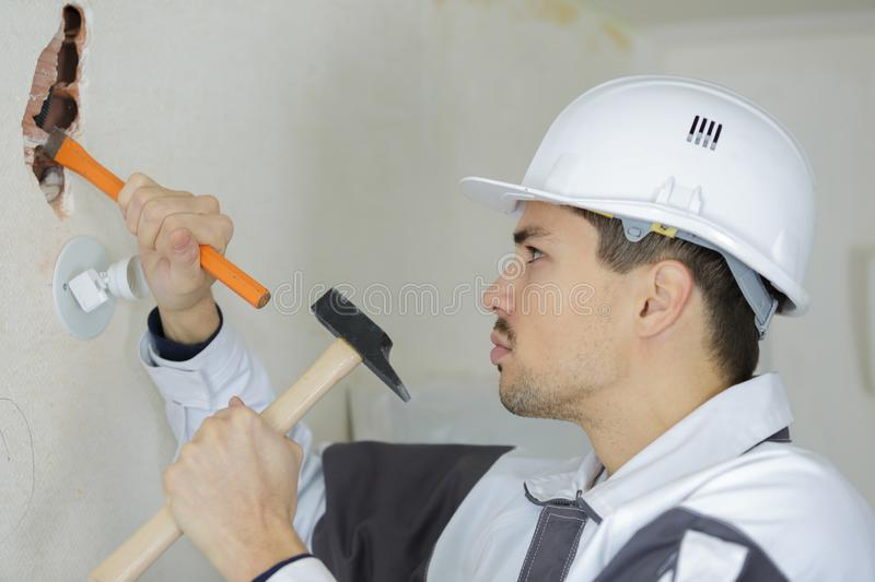 Photo depicts man with chisel and hammer royalty free stock image