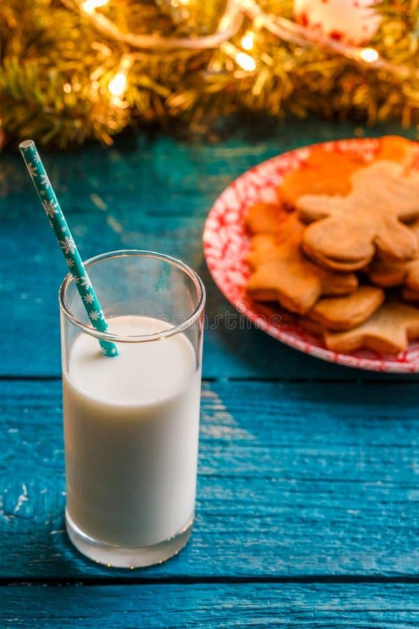 Photo des biscuits de gingembre, verre de lait, branches impeccables avec la guirlande brûlante photos stock