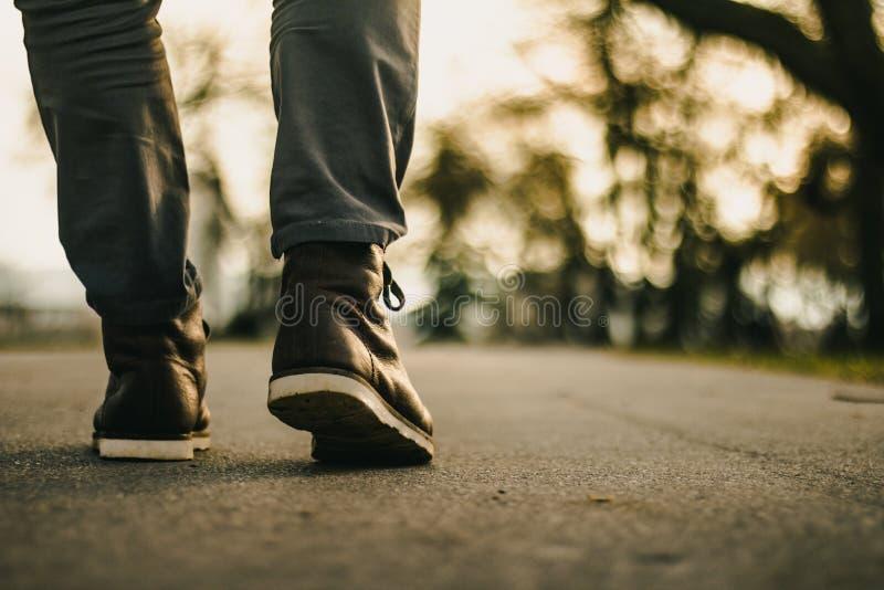 Photo des bottes en cuir brunes sur la route photo stock