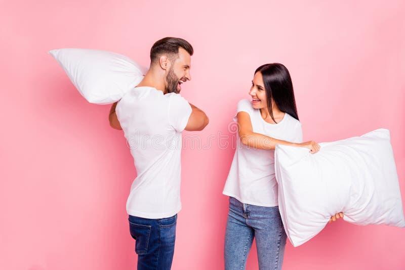 Photo des couples ayant décidé de se tuer avec des oreillers tandis que d'isolement avec le fond rose image libre de droits