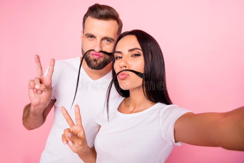 Photo des couples géniaux drôles des amis ayant l'amusement te montrant le v-signe avec le bâton tandis que d'isolement avec le f image libre de droits