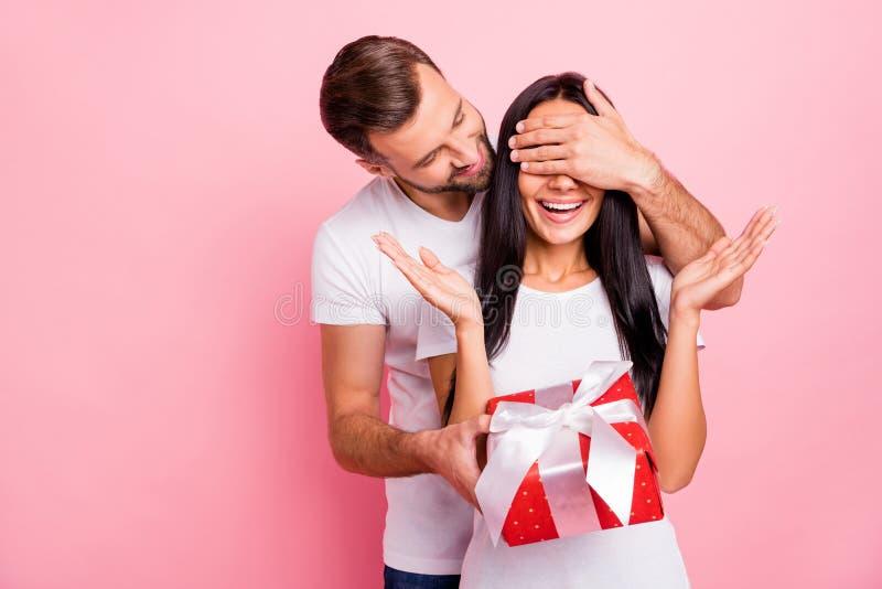 Photo des couples gentils mignons d'amoureux aimant au cadeau paquet rouge avec l'arc tandis que d'isolement avec le rose photos libres de droits