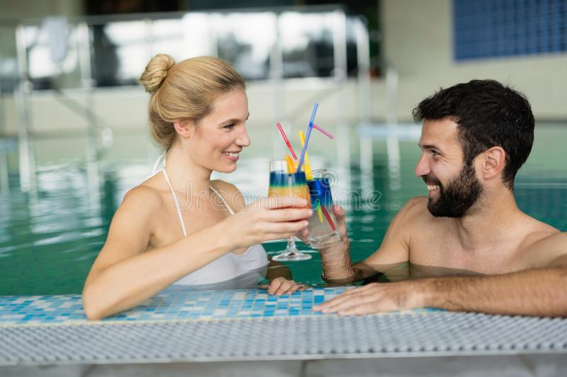 Photo des couples heureux détendant dans la piscine photo stock