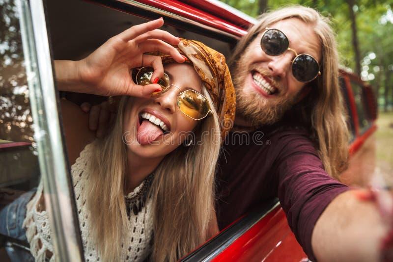 Photo des couples hippies caucasiens souriant, et dupant autour du whi photo libre de droits