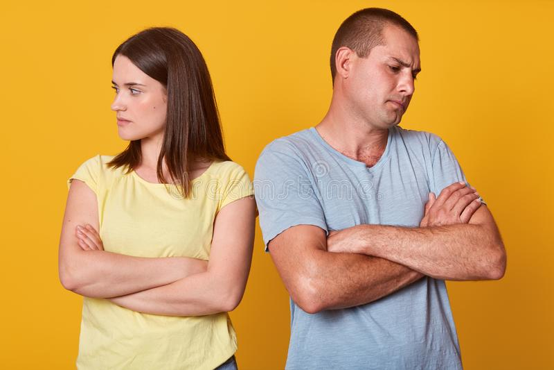 Photo des couples malheureux, homme et femme, se tenant avec le visage tourné à partir de l'un l'autre, avec des bras pliés, être photo stock