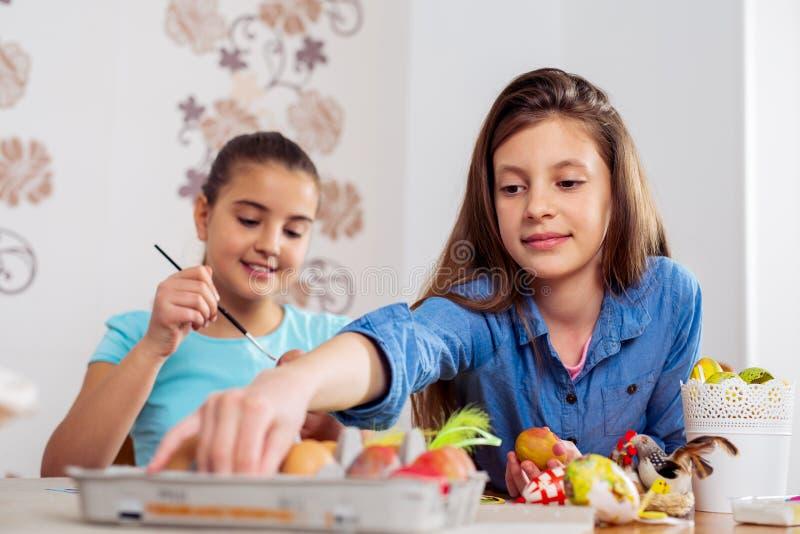 Photo des enfants mignons peignant des oeufs de pâques à la maison photographie stock libre de droits