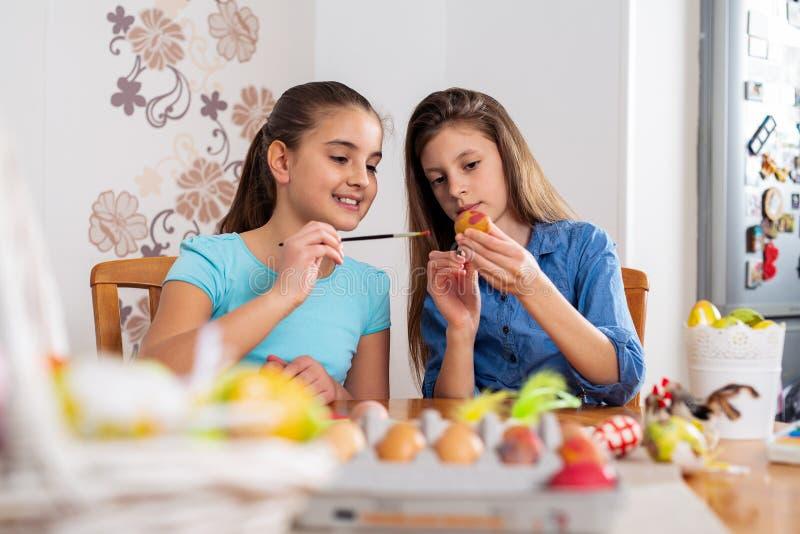 Photo des enfants mignons peignant des oeufs de pâques à la maison photos libres de droits