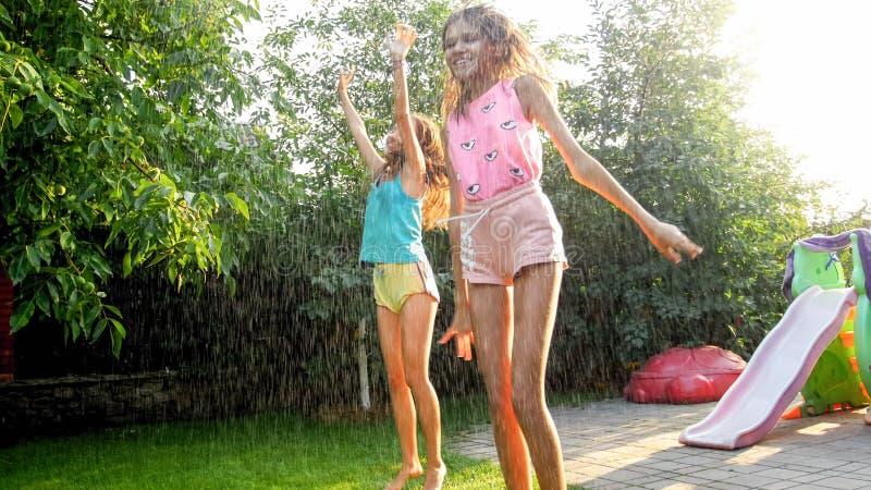 Photo des enfants riants heureux dans des v?tements humides sautant et dansant sous la pluie chaude au jardin Famille jouant et a images libres de droits