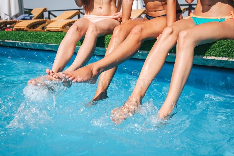 Photo des jambes du ` s de femme dans l'eau de éclaboussement moyenne dans la piscine D'autres modèles de remorquage sont calmes  photos libres de droits