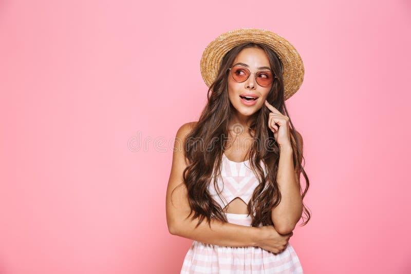 Photo des lunettes de soleil de la femme 20s et du smil de port élégants de chapeau de paille images stock