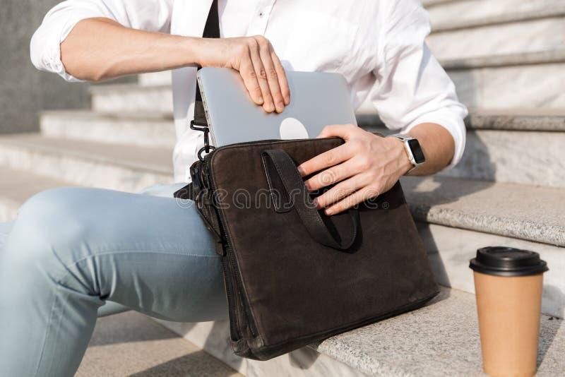 Photo des lunettes de soleil de port de l'homme d'affaires 30s, mettant l'ordinateur portable dans images stock
