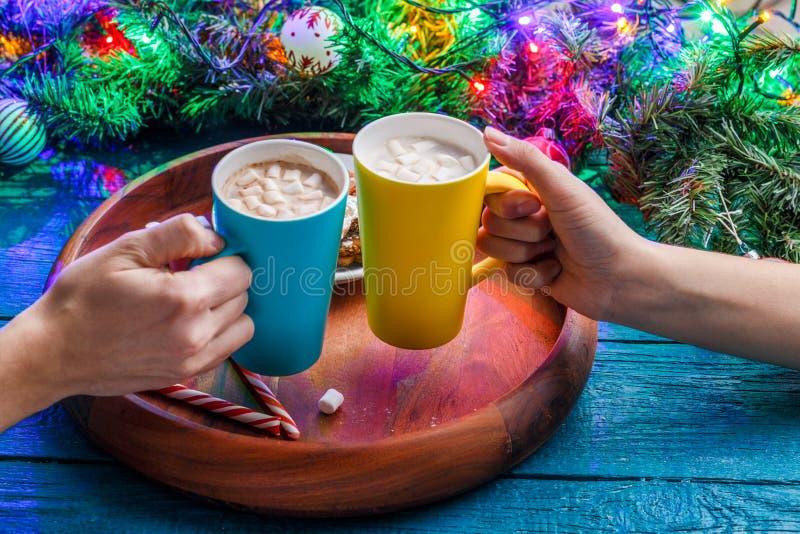 Photo des mains avec deux piles de cacao avec la guimauve sur la table photo libre de droits