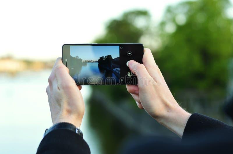 Photo des mains du ` un s d'homme tenant le téléphone et prenant la photo d'une rivière photo stock