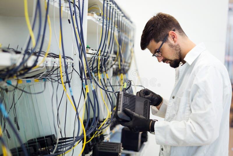 Photo des modems d'essai de technicien de réseau dans l'usine photographie stock libre de droits