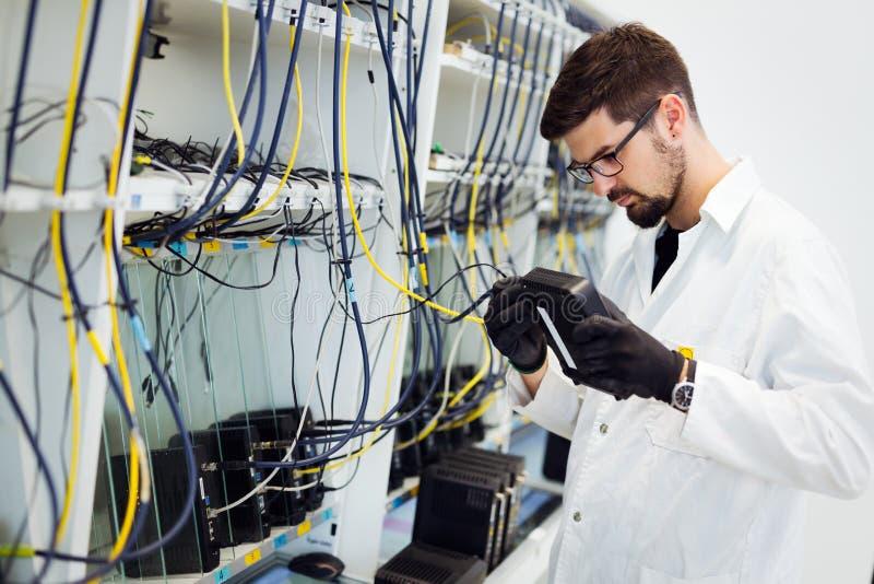 Photo des modems d'essai de technicien de réseau dans l'usine photo libre de droits