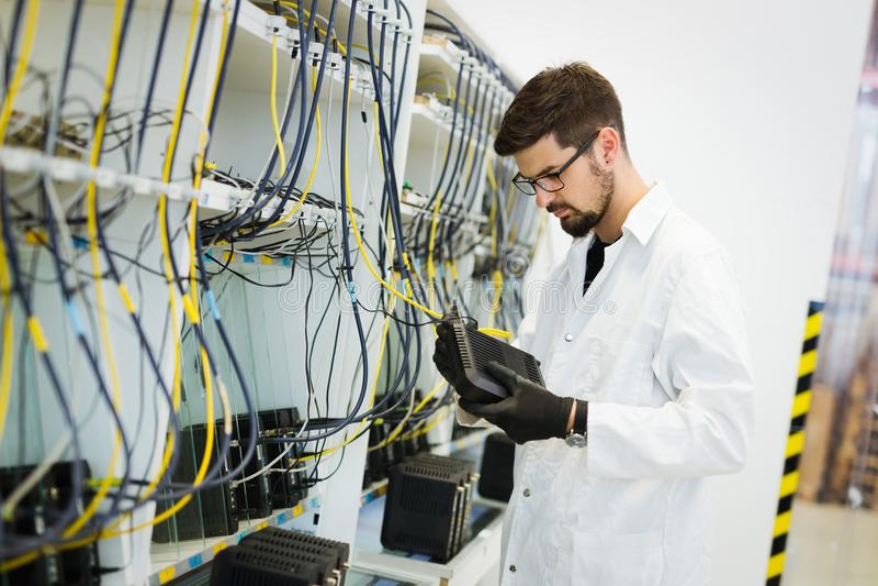 Photo des modems d'essai de technicien de réseau dans l'usine images stock