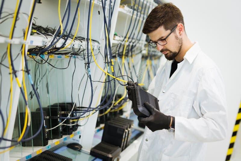 Photo des modems d'essai de technicien de réseau dans l'usine image libre de droits