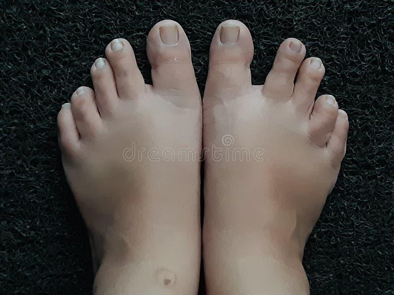 Photo des pieds sur un tapis de porte noir photographie stock libre de droits