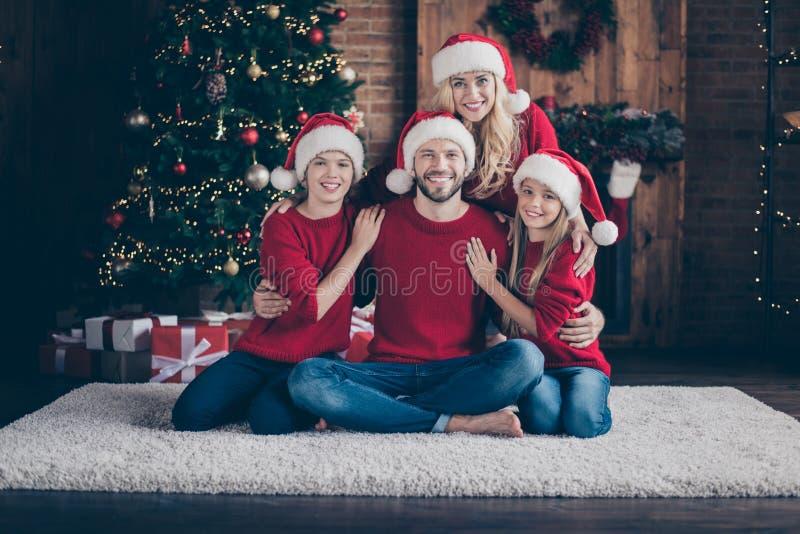 Photo des quatre grands membres de la famille père mère frère soeur de la mère de famille passer la veille de Noël ensemble, assi photo libre de droits
