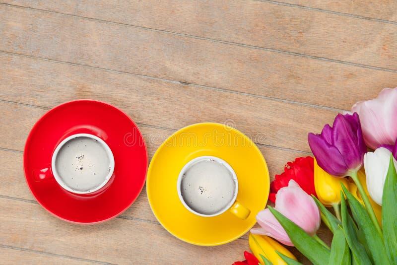Photo des tasses de café et de tulipes colorées sur le merveilleux photo libre de droits