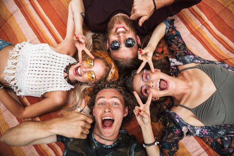 Photo des types attirants et des filles de hippies riant, et o menteur images stock
