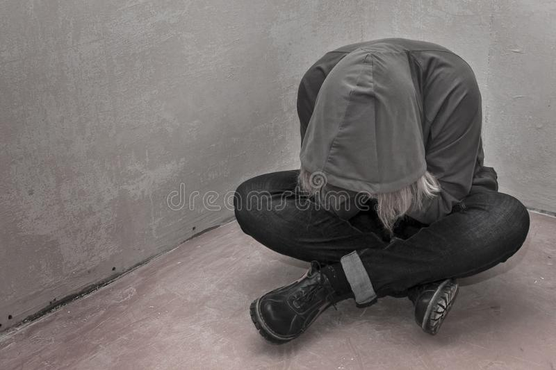 Photo of desperate young drug addict wearing hood and sitting alone in corner royalty free stock photo