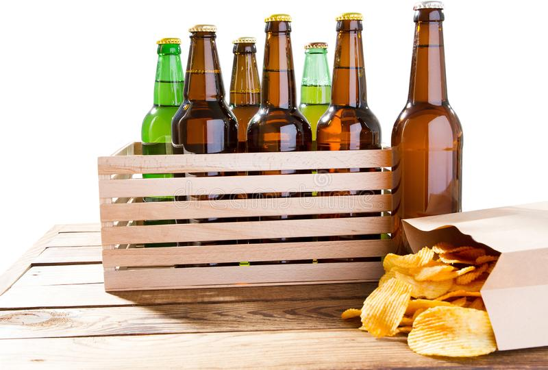 Photo of different full beer bottles with no labels and paper pack of potato chips on table.  royalty free stock image