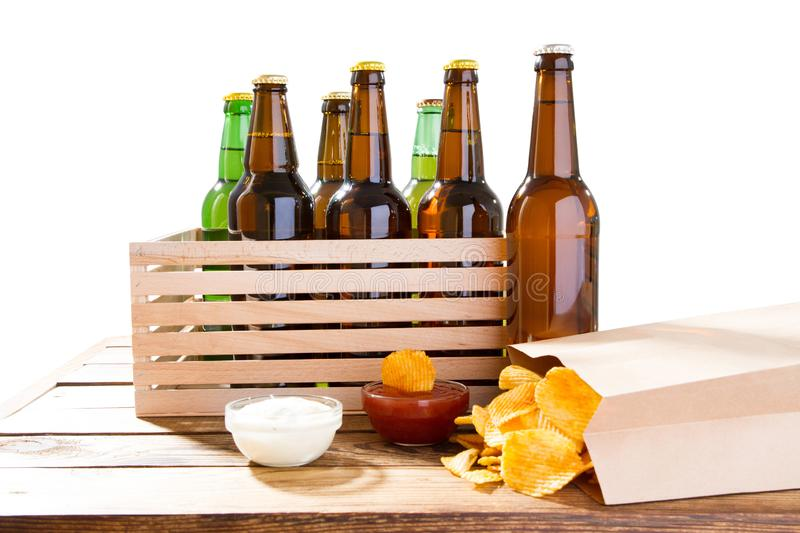 Photo of different full beer bottles with no labels and paper pack of potato chips on table, souces.  royalty free stock images