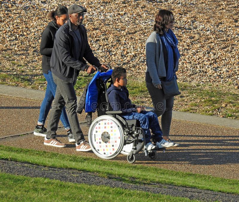 Disabled wheelchair user at beach. Photo of disabled child in wheelchair with family carers at a kent seaside location oct 2017 royalty free stock photo