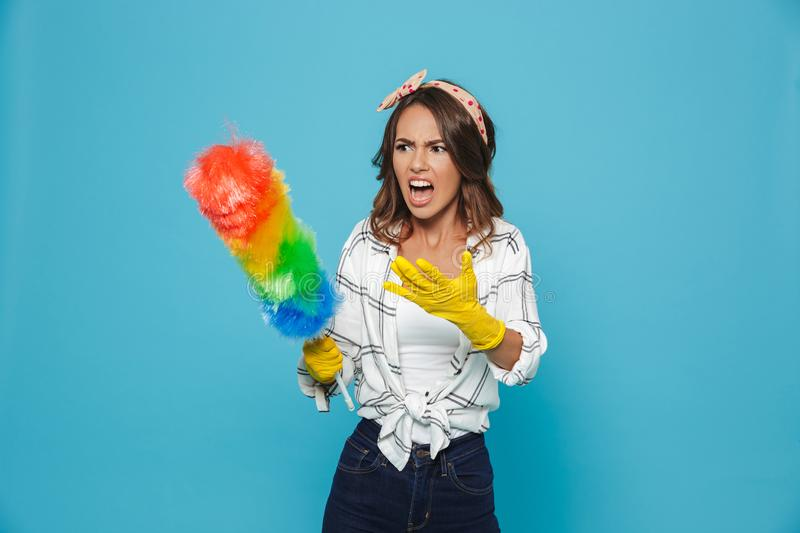 Photo of dissatisfied european housemaid 20s in yellow rubber gloves for hands protection screaming and holding colorful duster b stock image
